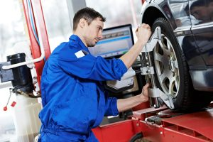 Mechanic checking wheel alignment