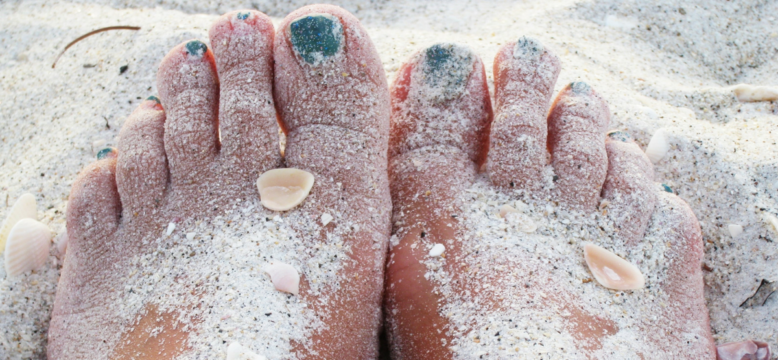 Feet covered in sand on the beach