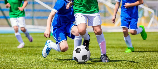 Young Soccer Players Running After the Ball.